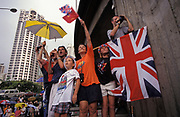 A British family hoping to catch a glimpse of passing VIPs, wave Union Jack flags on the eve of the handover of sovereignty from Britain to China, on 30th June 1997, in Hong Kong, China. That night signified the end of British rule, and the transfer of legal and financial authority back to China. Hong Kong was once known as 'fragrant harbour' (or Heung Keung) because of the smell of transported sandal wood.