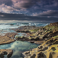 Low tide at La Jolla Cove near San Diego, sun breaking through to nicely light breaking waves and rocks.