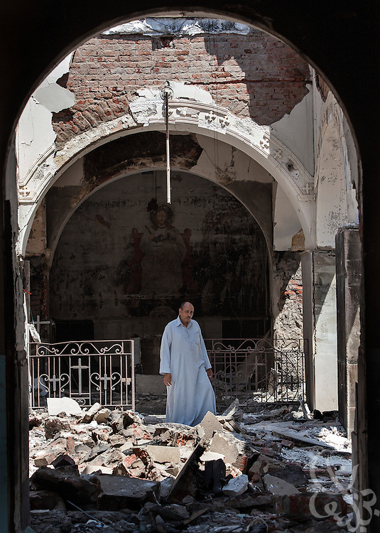 A Coptic Christian Egyptian man walks through the burned and looted Monastery of Emir Tadros church (est, 1598) August 20, 2013 after a recent attack by Muslims in the village of Nazla, located near el Fayoum, around a 100 kilometers South of Cairo, Egypt.  Christian villagers report 2 churches and a monastery in the area came under attack by their Muslim neighbors on the same day as Egyptian security forces were moving to forcibly disperse the sit-in camp of the supporters of deposed president Mohamed Morsi.