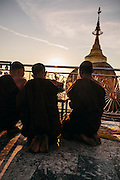 Monks prayer at sunset at Kyaiktiyo Pagoda (Golden rock)). Mon State, Myanmar