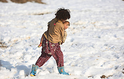 A girl carrying her little sister walks in snow in Kabul, Afghanistan. More than 8.4 million Afghan children, of whom 39 percent are girls, presently attend school, while 4.2 million others have no access to school mainly due to security reasons and poverty, January 13, 2013. Photo by Imago / i-Images...UK ONLY