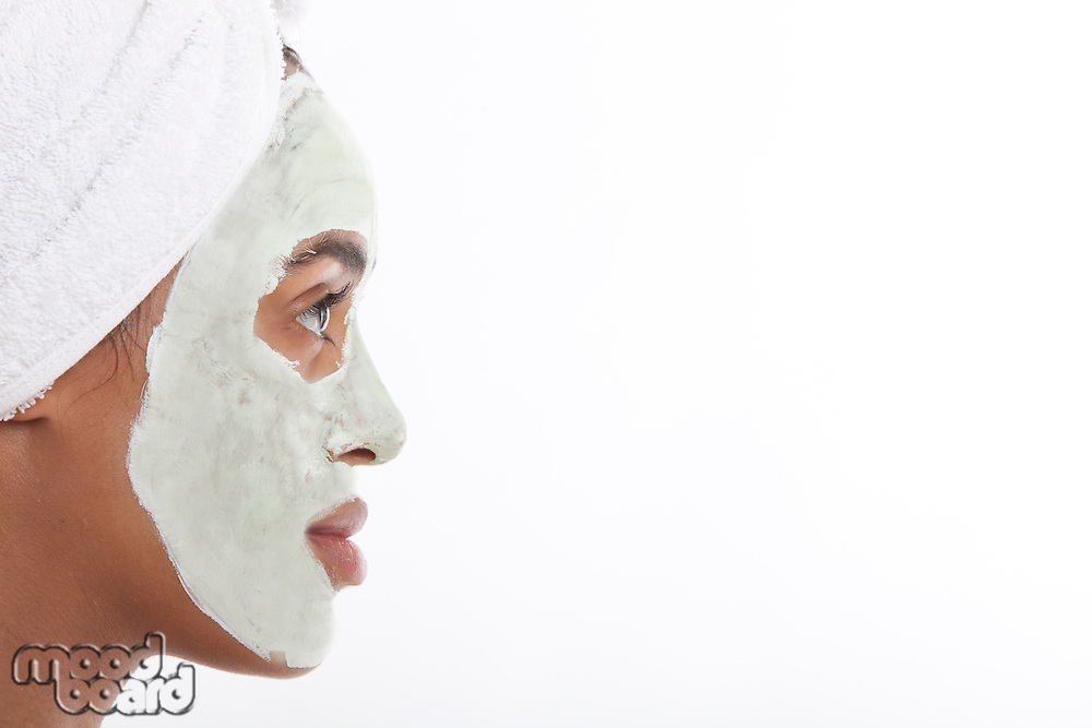 Profile shot of young Mixed Race woman with face pack against white background