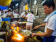 15 OCTOBER 2015 - BANGKOK, THAILAND: Thai candy makers cook peanut brittle like snacks during the Vegetarian Festival at the Joe Sue Kung Shrine in the Talat Noi neighborhood of Bangkok. The Vegetarian Festival is celebrated throughout Thailand. It is the Thai version of the The Nine Emperor Gods Festival, a nine-day Taoist celebration beginning on the eve of 9th lunar month of the Chinese calendar. During a period of nine days, those who are participating in the festival dress all in white and abstain from eating meat, poultry, seafood, and dairy products. Vendors and proprietors of restaurants indicate that vegetarian food is for sale by putting a yellow flag out with Thai characters for meatless written on it in red.    PHOTO BY JACK KURTZ