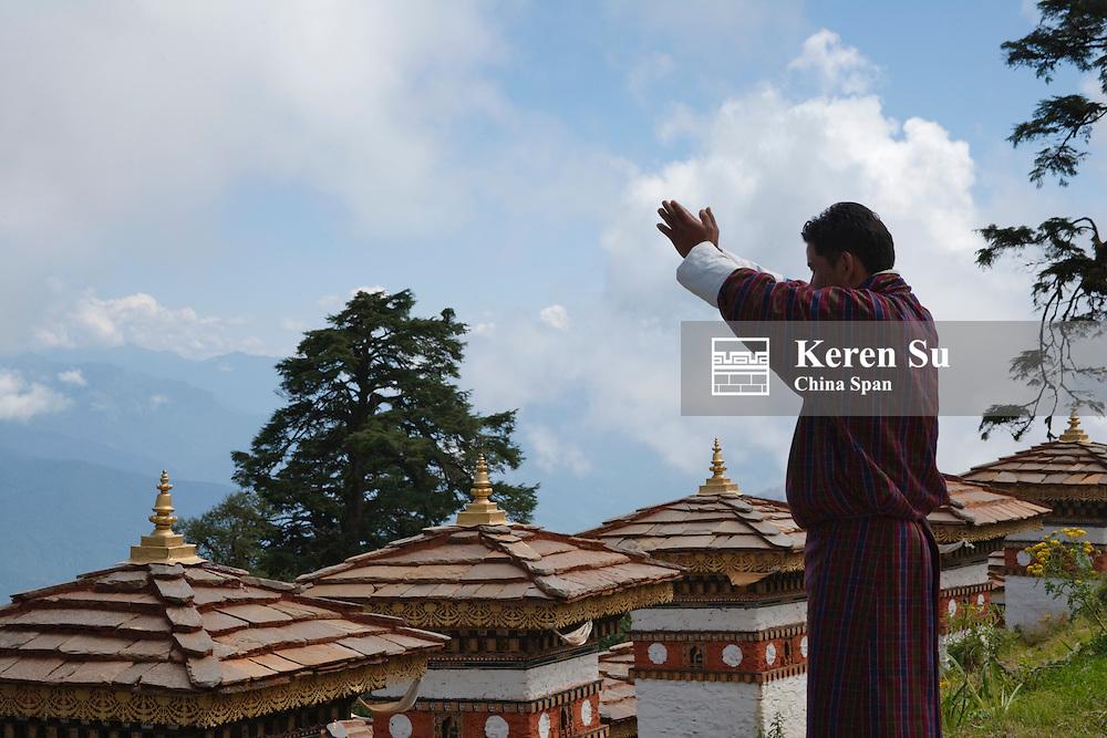 Pilgrim praying towards Sindokha Dzong, Dochu La Pass, between Thimphu and Punakha, Bhutan