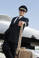Asian male pilot leaning at suitcase in front of airplane, elevated view.