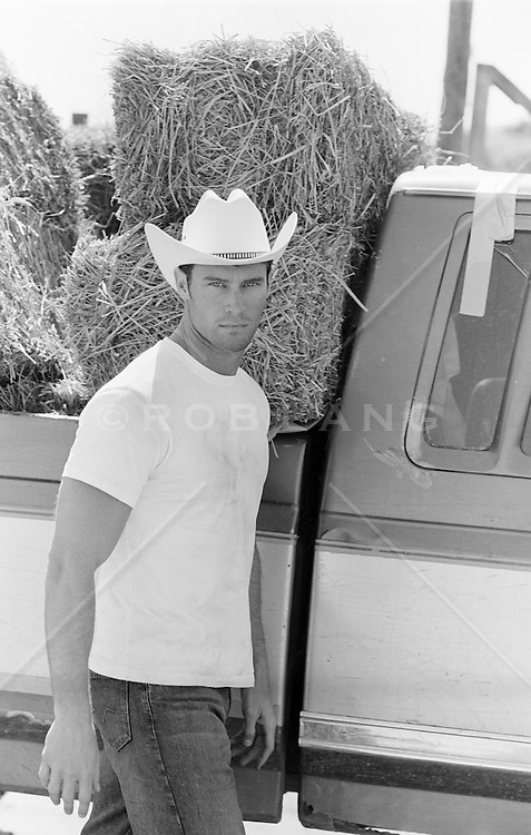 All American cowboy by a truck filled with hay