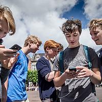 Nederland, Haarlem, 12 juli 2016.<br /> Jongeren spelen Pokemon Go op de Grote Markt in Haarlem.<br /> In het spel zie je een kaart van je omgeving. Van tijd tot tijd verschijnen er Pokémon, die je aanklikt en vervolgens kunt proberen te vangen met een zogeheten Pokéball. Zodra je hem vangt, wordt hij toegevoegd aan de lijst met Pokémon, ook wel een Pokédex genoemd. Deze lijst bestaat uit 150 Pokémon, de 150 die we kennen uit de eerste serie. In eerste instantie zie je hier alleen nummers op, maar door Pokémon te vangen, veranderen de nummers in plaatjes.<br /> Daarnaast is het mogelijk om een team te kiezen. Hierbij kun je kiezen uit team geel, rood of blauw. Bij een zogeheten gym kun je met andere Pokémon vechten, in de hoop de gym over te nemen voor jouw team.<br /> <br /> <br /> Teenagers  playing Pokemon Go in Haarlem. The game allows players to capture, battle, and train virtual creatures, called Pokémon, who appear throughout the real world. It makes use of GPS and the camera of compatible devices. The game is free-to-play, although it supports in-app purchases of additional gameplay items. An optional companion Bluetooth wearable device is planned for future release, the Pokémon Go Plus, and will alert users when Pokémon are nearby.(source: Wikipedia)<br /> <br /> Foto: Jean-Pierre Jans