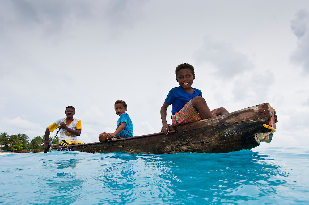Young boys in a dugout canoe, Rurbas, West Papua, Indonesia.