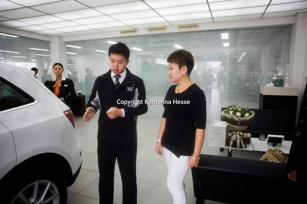 CHENGDU, 10/17/2012 :  Geschaeftsfrau Yang Xi, 37, laesst sich ihren neuen Wagen von einem Audimitarbeiter vorfuehren .