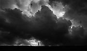 Young boy runs along the top of a sea wall on the North Sea coast as a storm approaches in De Haan, Belgium (1988)