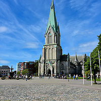 Kristiansand Cathedral at Town Square in Kristiansand, Norway <br /> The 230 foot clock tower of the Kristiansand Cathedral grabs your attention when you enter the town square. Then you begin to notice other features of Torvet such as its cobblestones, flowers, park benches, a large water fountain, small restaurants tucked inside historic buildings and the Rådhuset or Town Hall along the eastern border. Wonderful outdoor concerts are also staged here during the summer.