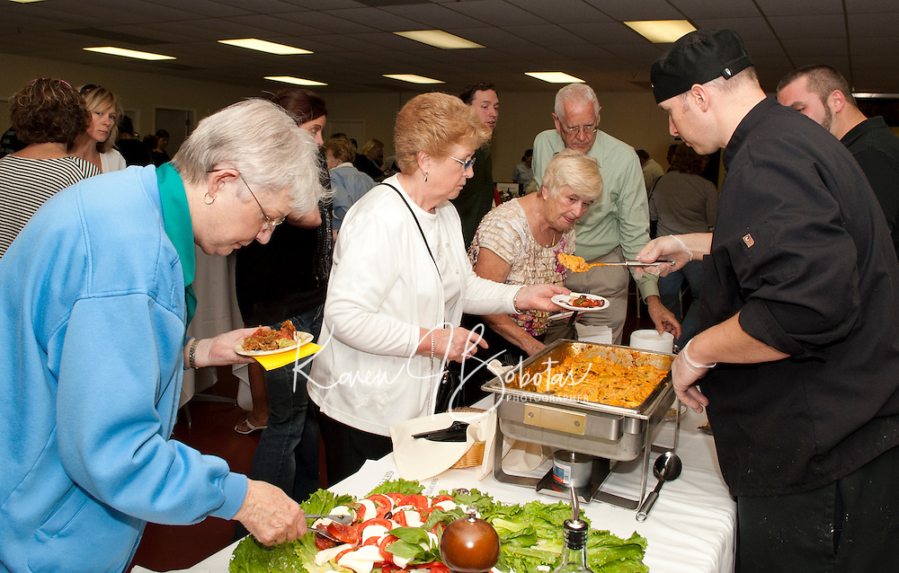 Fratello's Chef Rob Clifford offers Caprese Salad and Ravioli Florentine to Lorna McEwen and Lorraine Cahill during the Altrusa of Laconia's 22nd annual Taste of the Lakes Region Sunday afternoon at the Conference Center at Lake Opechee Inn and Spa.  (Karen Bobotas/for the Laconia Daily Sun)