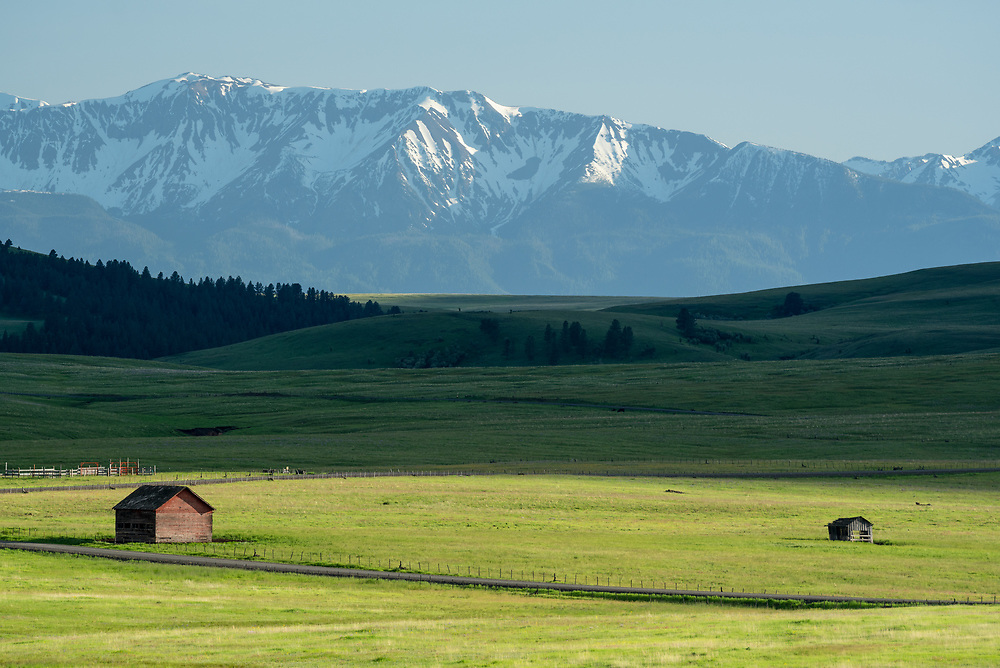 Old barn and shed on Oregon's Zumwalt Prairie with the Wallowa Mountains in the background.