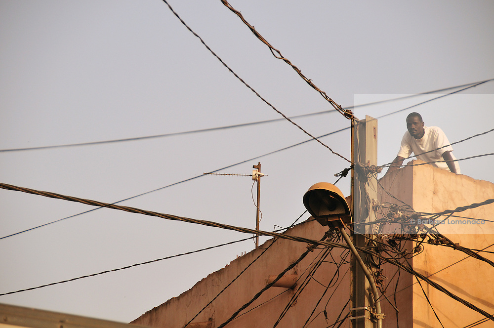 A man watches Fantani Touré singing from one of the roofs of Bozola district in Bamako