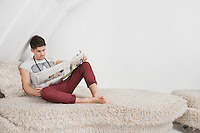 Young man reading newspaper while sitting on fur sofa