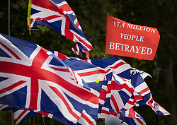 © Licensed to London News Pictures. 30/09/2019. London, UK. Union flags flutter next to a flag saying '17.4 MILLION PEOPLE BETRAYED' outside Parliament. Earlier a meeting of opposition leaders was held to discuss a plan to force the Prime Minister to go to Brussels to seek another Brexit delay as early as this weekend. Photo credit: Peter Macdiarmid/LNP