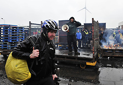 A Ford employee (Front) walks on his way to work as a protester shouts slogans backward at the entrance of the Ford Genk assembly factory, in Genk of Belgium, Jan. 9, 2013, the first day to resume the production in 2013. A thin majority of workers voted to re-start to work for 40 more days in 2013 in an agreement between the direction and unions earlier in the week, but some others decided to block all access to the plant in protest. Ford Europe announced on October 24, 2012 to close its Genk plant at the end of 2014, threatening 4,300 jobs as slumping demand across Europe leaves companies with too much capacity, Brussels, Belgium, January 9, 2013. Photo by Imago / i-Images...UK ONLY