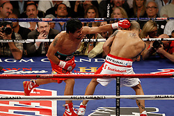 Nov 14, 2009; Las Vegas, NV, USA; Manny Pacquiao (orange trunks) and Miguel Cotto (white trunks) trade punches during their 12 round bout at the MGM Grand Garden Arena in Las Vegas, Nevada.  Mandatory Credit: Ed Mulholland/HBO