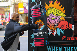 © Licensed to London News Pictures. 08/11/2016. New York CIty, USA. An Anti-Trump activists hits a punchbag featuring a Donald Trump's cartoon as he campaigns near Union Square in New York City on Tuesday, 8 November, the day of the presidential election in the United States of America. Photo credit: Tolga Akmen/LNP