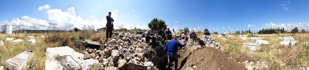Palestinian men dig a grave in a rfugee camp inTyre, Lebanon