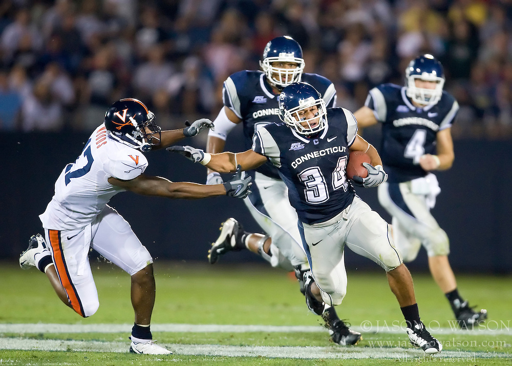 Connecticut running back Donald Brown (34) delivers a stiff arm to Virginia safety Brandon Woods (17).  Brown amasses a total of 206 yards rushing, including this 63 yard touchdown run.  The Connecticut Huskies defeated the Virginia Cavaliers 45-10 in NCAA football at Rentschler Field in East Hartford, CT on September 13, 2008.