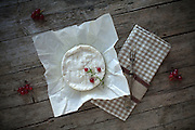 Overhead shot of Camembert cheese on piece of paper, decorated with redcurrants and thyme.