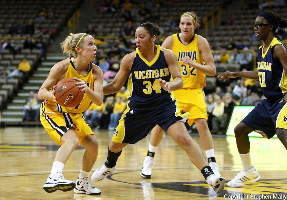 26 JANUARY 2009: Iowa guard Kristi Smith (11) looks up at the basket while being defended by Michigan guard Jessica Minnfield (34) during the first half of an NCAA women's college basketball game Monday, Jan. 26, 2009, at Carver-Hawkeye Arena in Iowa City, Iowa. Iowa defeated Michigan 77-69.