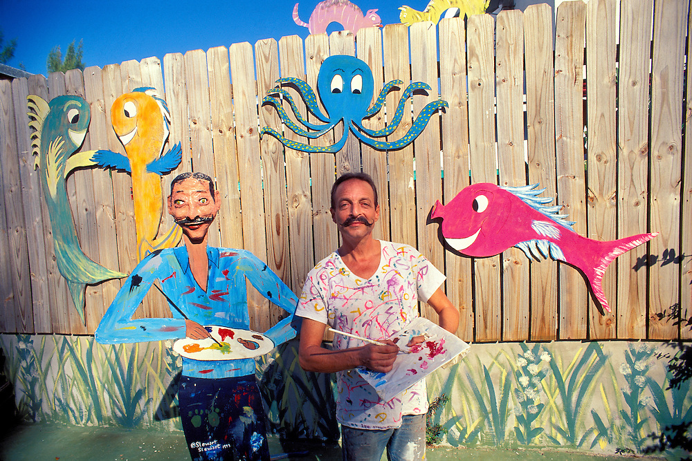Artist, teacher and activist Steart Stewart with a wooden cut-out, self-portrait statue, plus additional cut-outs he made of fish and various other creatures, in front of his South Beach home.