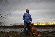 "Mike Gamble has lived on the Missouri River just east of Cooper's Landing since the early 1980's.  He had to rebuild his home after the flood of 1993, but nothing has diminished his love for living on the water.  ""It's one of the prettiest places on earth,"" says Gamble.  During warmer months he fishes and takes long walks with his dogs Max (pictured) and Mandy.  ""It's like being on vacation everyday."""