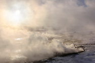 Fumaroles and hot springs with smoke on a sunny winter morning, geothermal area Hveravellir, Highlands, Icland