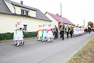 The Superkokot, a Sorbian tradition, is a harvest celebration where all 'Erntekönige' (Harvest King) fight for the title of the Super-Kral. The contestants are accompanied by their 'Ernteköniginnen' (Harvest Queens).<br /> The 3-year-old cock named 'Heinrich II' had already been dead when he got attached to the oak portal. The contestants have to ripp off the head first, then the wings.<br /> In the end, a living cock has to be caught by the contestants, but this cock is designated to live on.