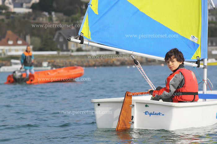 The Optimist is a small, single-handed sailing dinghy intended for use by children up to the age of 14. Nowadays boats are usually made of fiber reinforced plastic, although wooden boats are still built. It is one of the most popular sailing dinghies in the world, with over 140,000 boats officially registered with the class and many more built but never registered. The Optimist is recognized as an International Class by the International Sailing Federation. Picture was taken in some watersports centers in Brittany, France.