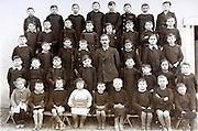 vintage formal group photo of school children with teacher