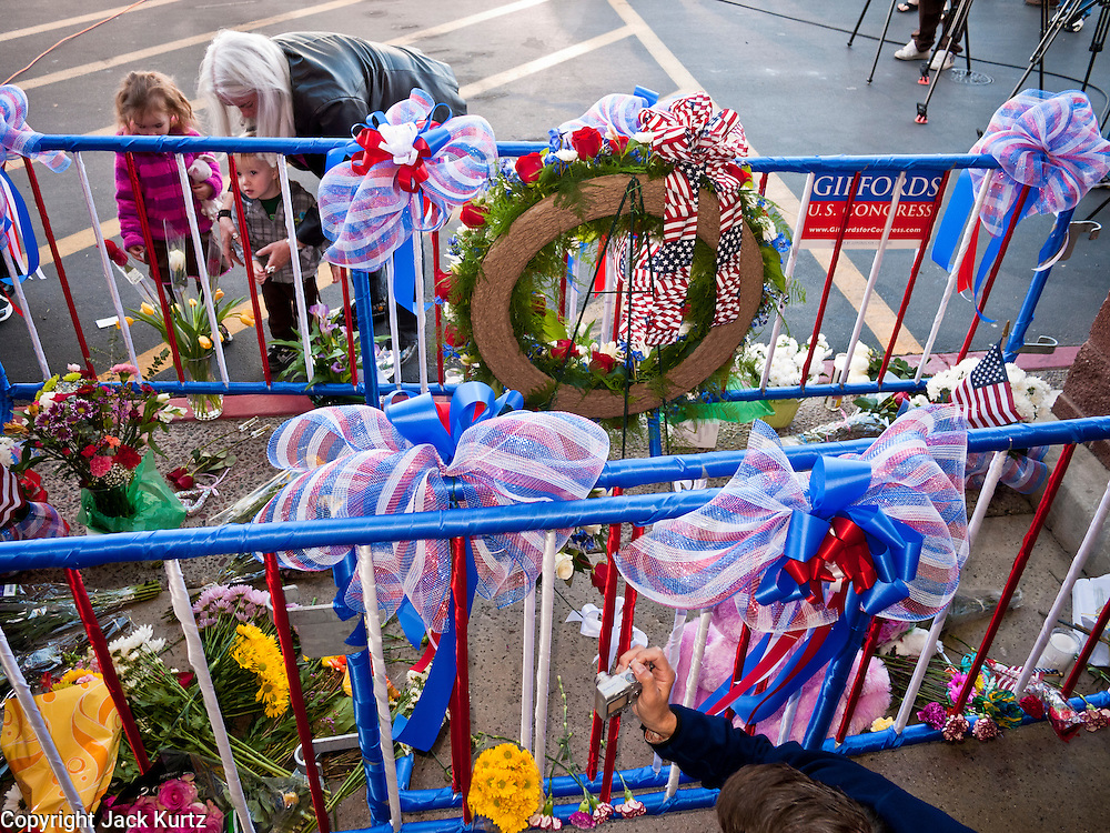 """15 JANUARY 2010 - TUCSON, AZ:    People visit the memorial for victims of the mass shooting in Tucson, AZ, Saturday, January 15. Six people were killed and 14 injured in the shooting spree at a """"Congress on Your Corner"""" event hosted by Arizona Congresswoman Gabrielle Giffords at a Safeway grocery store in north Tucson on January 8. Congresswoman Giffords, the intended target of the attack, was shot in the head and seriously injured in the attack but is recovering. Doctors announced that they removed her breathing tube Saturday, one week after the attack. The alleged gunman, Jared Lee Loughner, was wrestled to the ground by bystanders when he stopped shooting to reload the Glock 19 semi-automatic pistol. Loughner is currently in federal custody at a medium security prison near Phoenix.   PHOTO BY JACK KURTZ"""