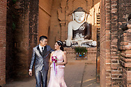 After having worshipped the Bhudda inside the Phyathada Pagoda in Bagan, Myanmar, this just married young burmese couple is going out from the temple to celebrate the wedding day with family and friends.<br />
