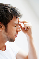 Man with Headache touching forehead