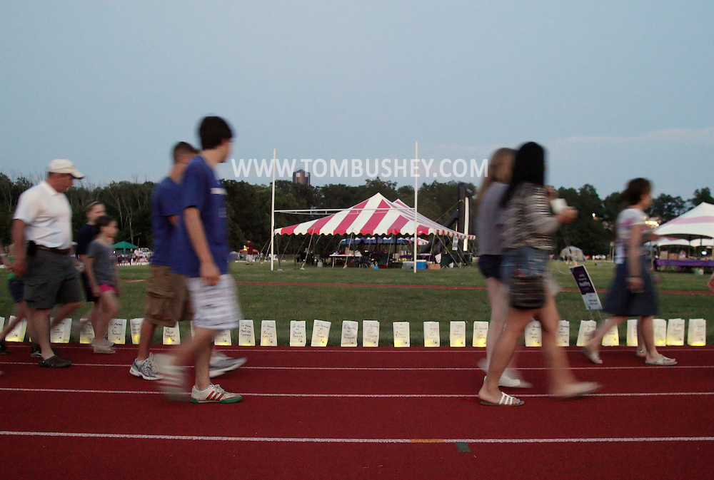 Goshen, New York - People walk laps around the track, which is lined with luminaria in remembrance of cancer victims, during the Relay for Life at Goshen High School on June 19, 2011. The Relay for Life is the American Cancer Society's signature fundraising event. Participants celebrate the lives of people who have battled cancer, remember loved ones lost, and fight back against the disease by raising money.