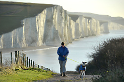 © Licenced to London News Pictures. 18th December 2017. Cuckmere Haven, East Sussex. Paddle boarders and dog walkers enjoyng the sight of golden sunlight lightng up the Seven Sisters chalk cliffs at Cuckmere Haven, near Eastbourne, East Sussex, on a brght crisp morning.  Photo credit: Peter Cripps/LNP