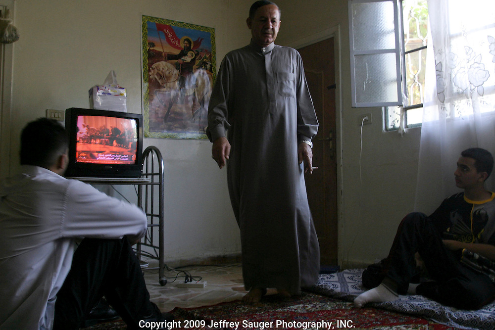 Emad Al-kasid, left, his brother Hussein, 15, and his father Malik, watch the first official meeting of Iraq's new government in his father's apartment in the Iraqi area of Damascus, Syria, Sunday, July 13, 2003. Al-kasid has been planning has been planning the trip home to Nasiriyah, Iraq, over the last year. He is visiting his immediate family is in Damascus, Syria, as hundreds of thousands of Iraqi Shiite settled in Syria after the Gulf War and their uprising against Saddam Hussein in 1991.
