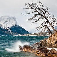 storm blows waves crashing down on the shore of saint mary's lake glacier national park, montana