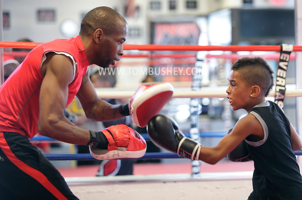 Terrence Thomas II, an 8-year-old boxer, trains with his father Terrance Thomas at the Newburgh Boxing Club on Wednesday, Aug. 8, 2012.