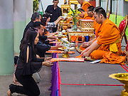 20 AUGUST 2015  - BANGKOK, THAILAND:     People make on offering of monks robes at the funeral for Yutnarong Singraw Thursday. More than 100 people gathered at Wat Bang Na Nok in Bangkok for the third day of the funeral rites for  Yutnarong Singraw, a Thai man who was killed in the bombing at the Erawan Shrine in Bangkok Monday. Yutnarong was delivering legal documents when the blast occurred. More than 20 people were killed and more than 100 injured in the blast.    PHOTO BY JACK KURTZ