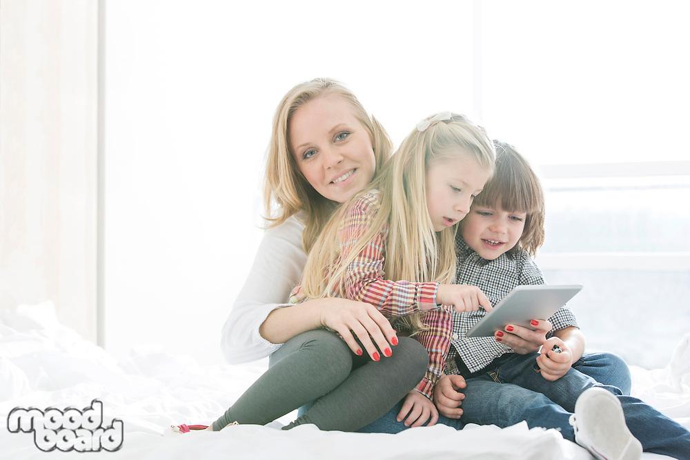 Portrait of happy mother with children using digital tablet in bedroom