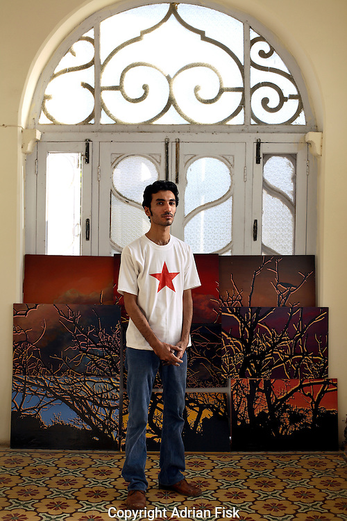 Asim Butt stands in his studio in Bhopal House in karachi. The painting behind titled 'View from Bhopal House' he had recently sold. The proceeds of which he was donating to the Karachi city district government so they could instal dustbins around the city.