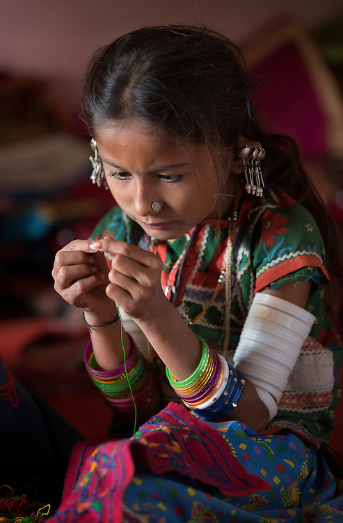 young tribal girl from Bhuj area of Gujarat threading a needle as she learns from a very young age the textile traditions of her culture