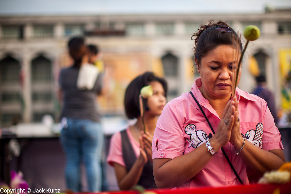 "01 JANUARY 2013 - BANGKOK, THAILAND:   People pray at a shrine during a special merit making ceremony at Bangkok City Hall New Year's morning. Many Thais go to Buddhist temples and shrines to ""make merit"" for the New Year. The traditional Thai New Year is based on the lunar calender and is celebrated in April, but the Gregorian New Year is celebrated throughout the Kingdom.    PHOTO BY JACK KURTZ"