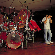 Simon Philips listening to his work. Red Tama Starclassic drum kit.