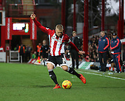 Brentford defender Jake Bidwell crossing the ball during the Sky Bet Championship match between Brentford and Milton Keynes Dons at Griffin Park, London, England on 5 December 2015. Photo by Matthew Redman.