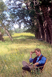 man sitting in a grove of trees and a field while he holds a book to his head in deep thought