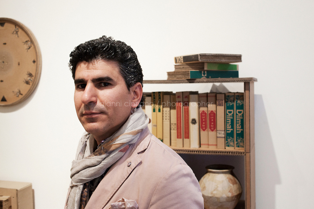 VENICE, ITALY - 1 JUNE 2013: Artist Yassen Wami (40), part of the artistic partnership WAMI, poses with his cardboard installation in a room of the Iraq Pavilion at Ca' Dandolo in Venice, Italy, on June 1st 2013. <br /> <br /> &quot;Welcome to Iraq&quot; is the  exhibition showcasing the works of eleven contemporary artists living and working inside Iraq curated by Jonathan Watkins, at the Iraqi Pavilion at the 55th International Art Exhibition of the Biennale di Venezia. <br /> <br /> Iraq is insinuated into the exhibition space at the Iraqi Pavillon, creating a salon atmoshpere where visitors can sit, read and learn about Iraqi culture and drink tea. In collaboration with the Iraqi National Library and Archive book and comica are available to read.<br /> <br /> The 55th International Art Exhibition of the Venice Biennale takes place in Venice from June 1st to November 24th, 2013 at the Giardini and at the Arsenale as well as in various venues the city. <br /> <br /> Gianni Cipriano for The New York TImes